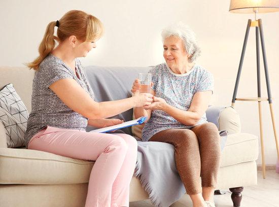 caregiver giving medicine to an elder woman