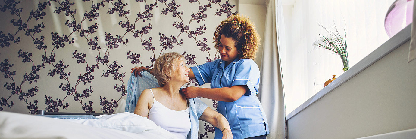 caregiver helping senior woman wear clothes